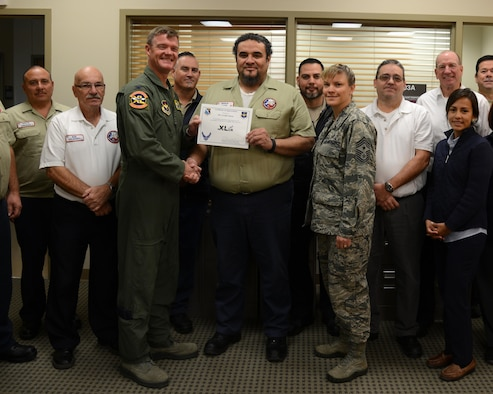 """Cecilio Saenz, center, 47th Maintenance Directorate quality assurance inspector, poses with Col. Thomas Shank, left, 47th Flying Training Wing commander, and Chief Master Sgt. Teresa Clapper, 47th FTW command chief, after accepting the """"XLer of the Week"""" award, here, Nov. 18, 2015. The XLer is a weekly award chosen by wing leadership and is presented to those who consistently make outstanding contributions to their unit and Laughlin. (U.S. Air Force photo by Airman 1st Class Brandon May)"""