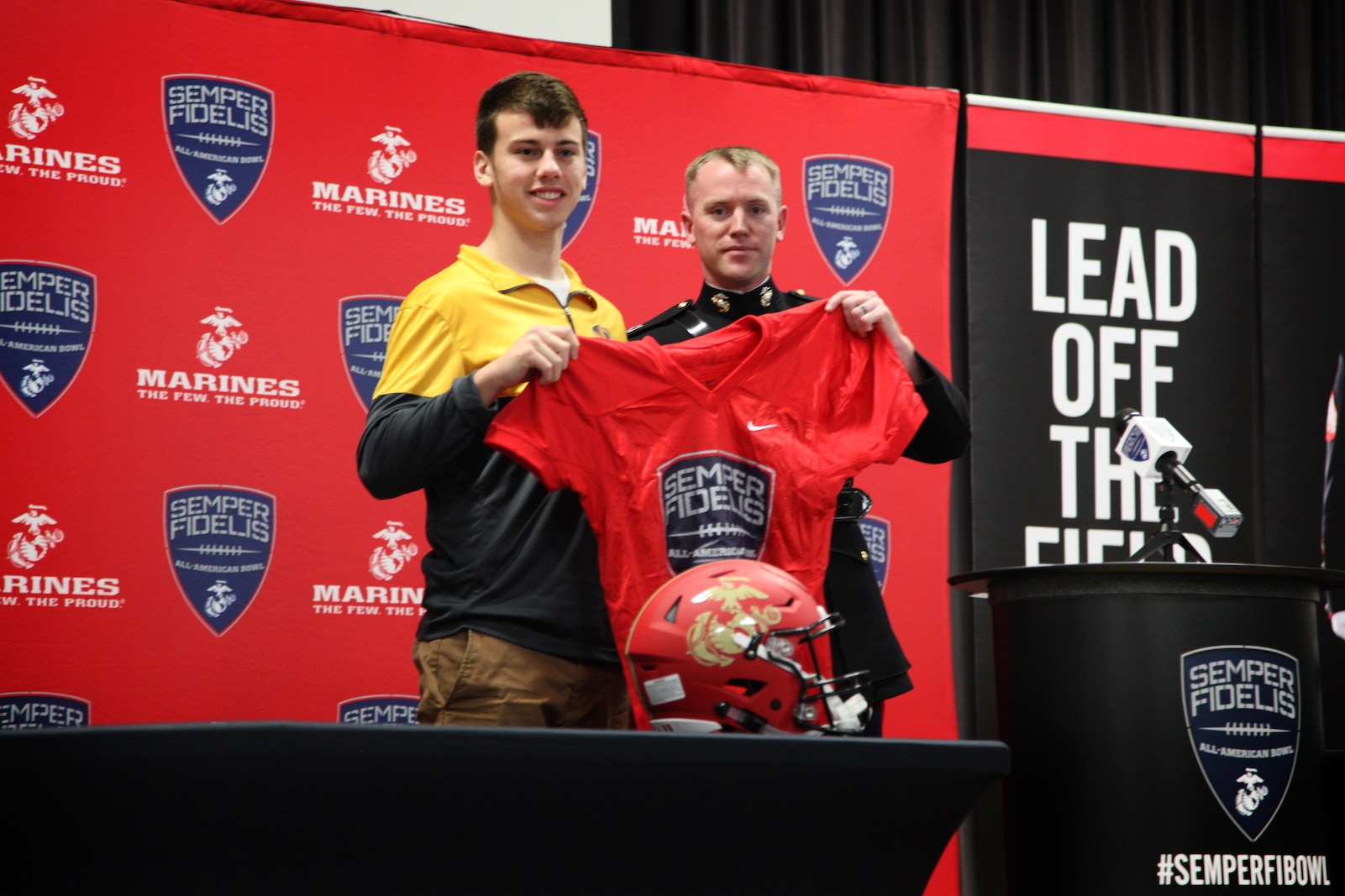 Capt. Ryan Kilkenny presents Tucker McCann his Semper Fidelis Bowl Game Jersey at a presentation at O'Fallon High School, O'Fallon, IL Dec. 2. Tucker, one of the top place kickers in the nation and University of Missouri commit, will play for the West Team during the 5th annual Semper Fidelis Bowl Game in Carson, CA.