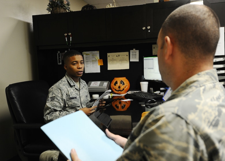 Senior Airman Mathan Simmons, 325th Comptroller Squadron financial services technician, assists and briefs an Airman before his deployment to an overseas location Nov. 25 at the Base Support Center. The Customer Support section manages the Defense Travel System, is responsible for leave management, and acts as the intermediary for non-DTS travel voucher computation serviced by the Air Force Financial Services Center. (U.S. Air Force photo by Senior Airman Ty-Rico Lea/Released)