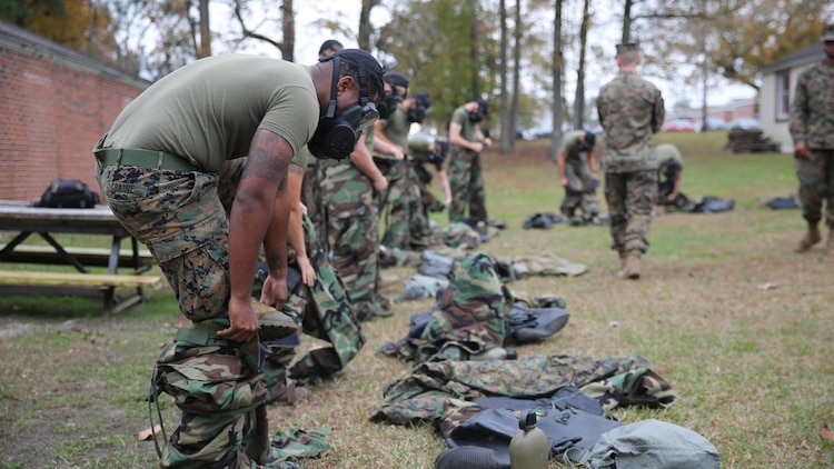 Marines with 2nd Transport Support Battalion get dressed in Mission Oriented Protective Posture gear during chemical, biological, radioactive and nuclear defense training held at Marine Corps Base Camp Lejeune, N.C., Dec. 1, 2015. Marines applied information obtained in classes about an active chemical threat and the proper protective equipment to decontaminate themselves in a CBRN situation.