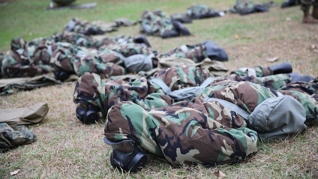 Marines with 2nd Transport Support Battalion lie in the prone position during a nuclear explosion simulation during chemical, biological, radioactive and nuclear defense training held at Marine Corps Base Camp Lejeune, N.C., Dec. 1, 2015. Marines applied information obtained in classes about an active chemical threat and the proper protective equipment to decontaminate themselves in a CBRN situation.