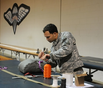 U.S. Army Spc. Christopher Locklear, with 824th Quartermaster Company, folds a T11 reserve parachute that will be used in Operation Toy Drop. (U.S. Army photo by Staff Sgt. Shaiyla Hakeem)