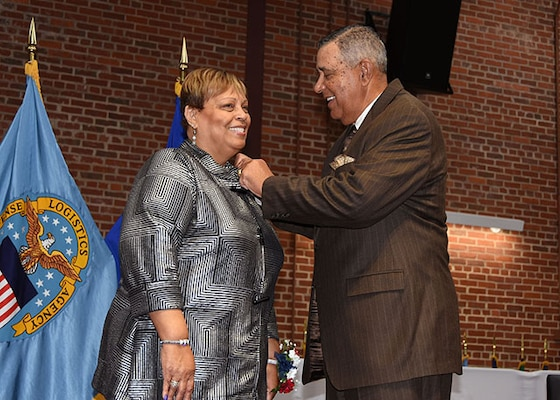 President of the American Federation of Government Employees Local 1992, Lucy Lewis receives her retirement pin from her brother, retired Navy Master Chief Petty Officer Thomas Keiser, during a ceremony Nov. 24, 2015 in the Frank B. Lotts Conference Center on the occasion of her retirement from federal service after 41 years.