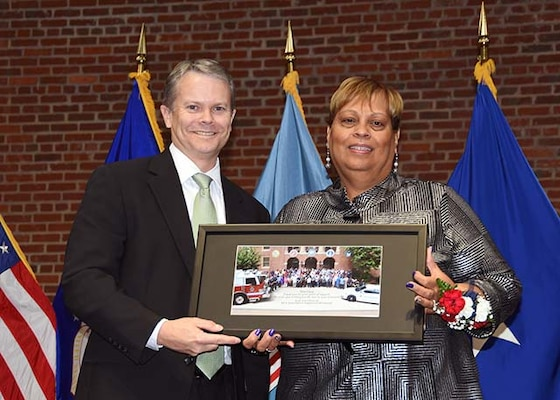 David Gibson, site director, DLA Installation Support at Richmond, Virginia, presents Lucy Lewis, president of the American Federation of Government Employees Local 1992, with a commemorative photo of installation support employees during a ceremony Nov. 24, 2015 in the Frank B. Lotts Conference Center on the occasion of her retirement from federal service after 41 years.