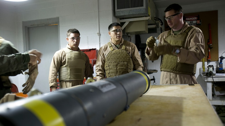 Chief Warrant Officer 2 Jason Scarborough, right, Master Sgt. Jerry Slattum, center, and Sgt. Ralph Confortini, all Explosive Ordnance Disposal technicians with EOD Company, finish donning personal protective equipment before disarming the Griffin missile at Marine Corps Base Camp Lejeune, N.C., Dec. 1, 2015. A Griffin missile is an air and ground-launched, precise, low collateral-damage missile used for irregular warfare operations.