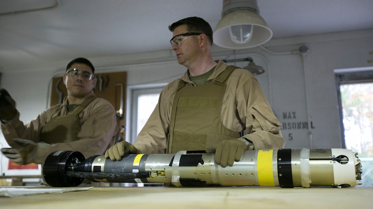 Chief Warrant Officer 2 Jason Scarborough, center, and Master Sgt. Jerry Slattum, both Explosive Ordnance Disposal technicians with EOD Company, diagnose the Griffin missile to reassure that the missile is safe to operate on at Mairne Corps Base Camp Lejeune, N.C., Dec. 1, 2015. Marines with EOD constantly work to develop procedures and familiarize themselves with new ordnance.