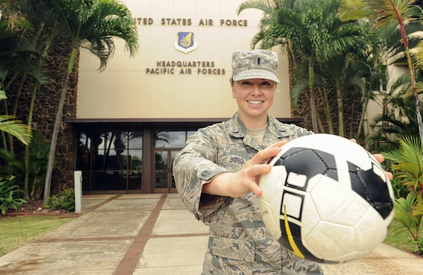 U.S. Air Force 1st Lt. Charity Borg, Headquarters Pacific Air Forces Protocol officer, poses with her soccer ball after returning from the Royal Air Force's AIRCOM Indoor Football Championship in the United Kingdom, Nov. 30, 2015, Joint Base Pearl Harbor-Hickam, Hawaii. Borg, goalie and captain for the U.S. Air Force women's team, was recruited to play after a long hiatus away from the sport, and the team took bronze in the tournament. (U.S. Air Force photo by Tech. Sgt. Amanda Dick/Released)