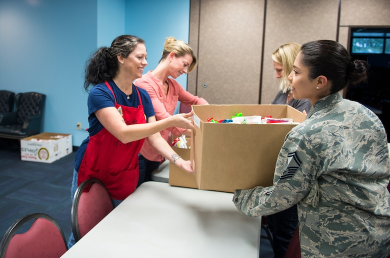 "Rachel Sumja, left, cookie drive event coordinator, hands a box of cookies to Senior Master Sgt. Mary Twitty, 23d Contracting Squadron first sergeant, during the Annual Airmen's Cookie Drive, Dec. 2, 2015, at Moody Air Force Base, Ga. Sumja, said ""although Airmen can easily go to the Base Exchange for cookies, it is still important to give Airmen something made with a personal touch and a taste of home."" (U.S. Air Force photo by Senior Airman Ceaira Tinsley/Released)"