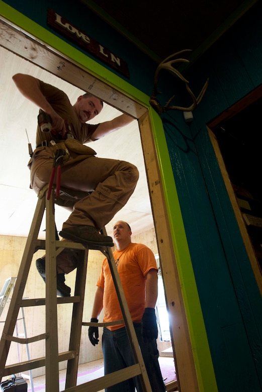 Staff Sgt. Jody Perkins, Air Force Center for Electronic Distribution and Systems developer, right, and Tech Sgt. Jonathan Kirby, AFCED noncommissioned officer in charge, nail wood paneling onto the walls of a bedroom in the battered and homeless women and children shelter Sept. 4, 2015 in Shorter, Ala. Hand's Off Women is a nonprofit organization that is aimed at promoting and protecting women's and children's human and civil rights, while eliminating violence against women. (U.S. Air Force photo by Airman 1st Class Alexa Culbert)