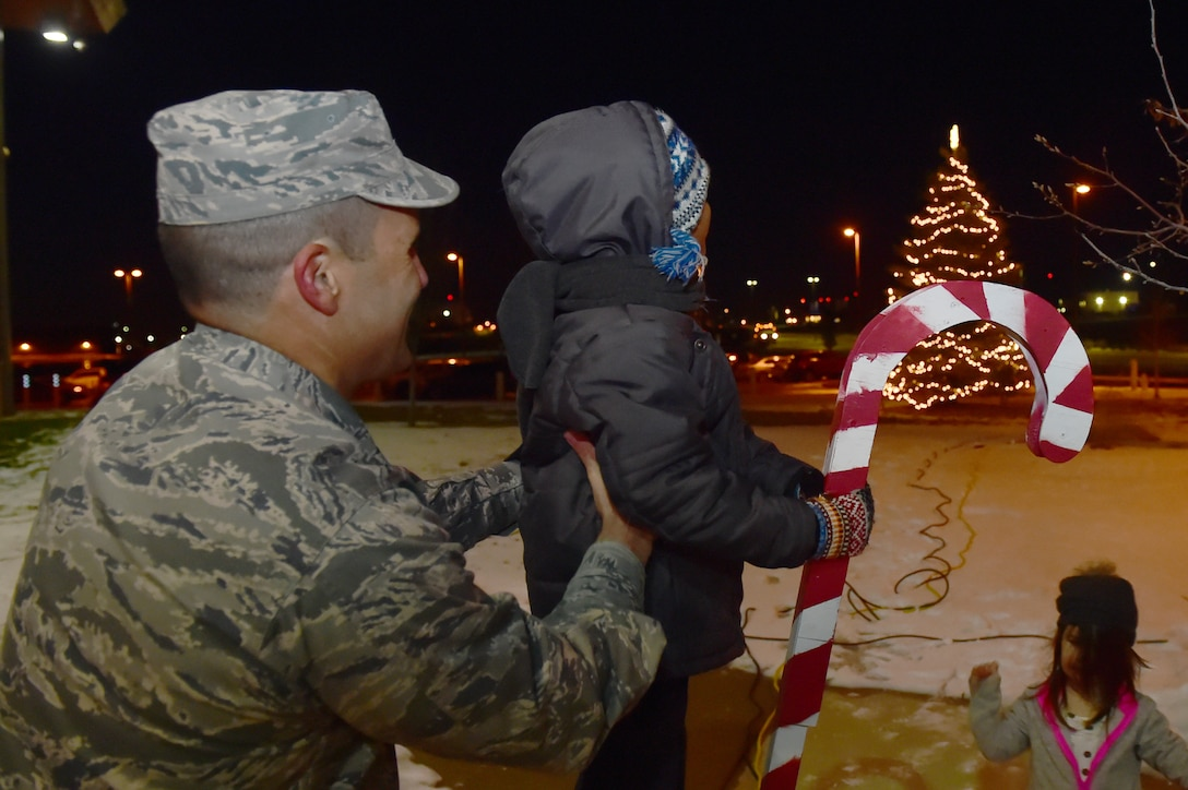 Col. John Wagner, 460th Space Wing commander, helps a child light the tree in front of the 460th SW Headquarters Building Dec. 2, 2015, on Buckley Air Force Base, Colo. Members of Team Buckley gathered to celebrate and enjoy refreshments in honor of the holiday season. (U.S. Air Force photo by Airman 1st Class Luke W. Nowakowski/Released)