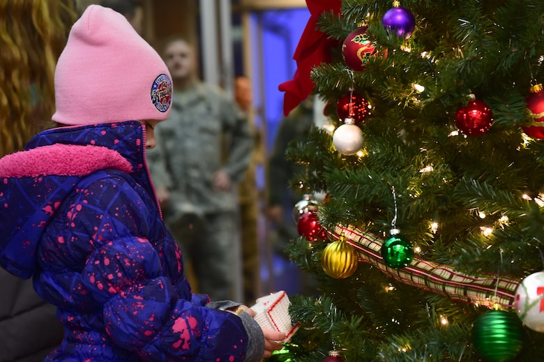 A child from the Buckley AFB community admires an ornament Dec. 2, 2015, on Buckley Air Force Base, Colo. Members of Team Buckley gathered for the annual tree-lighting ceremony which included carolers, refreshments and Santa Claus  to celebrate the holiday season. (U.S. Air Force photo by Airman 1st Class Luke W. Nowakowski/Released)