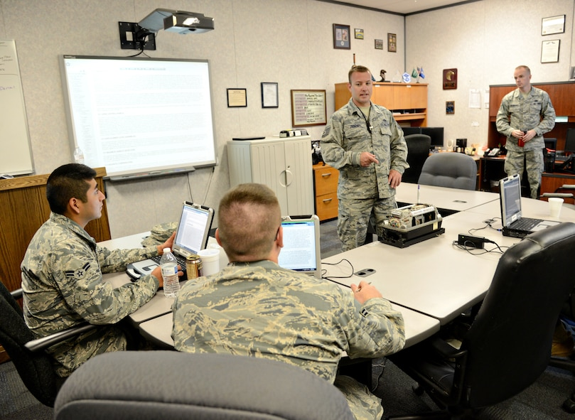 Tech. Sgt. Mitchell Zebert, center, teaches a class to students in the 373rd Training Reserve Squadron. Sergeant Zebert is currently an instructor-in-training and is observed by qualified instructors, such as Staff Sgt. Johnmartin Reynolds, right, during his classes. The instructors will contribute additional information to the students as needed to help him and other instructors-in-training how to more efficiently teach a subject area. (Air Force photo by Kelly White/Released)