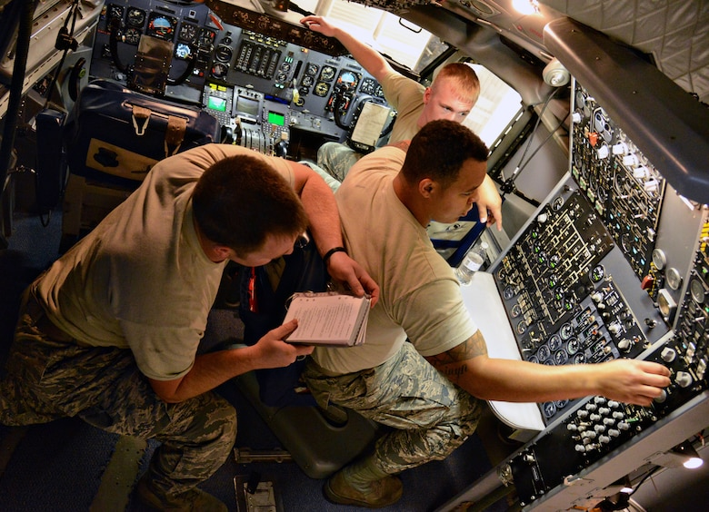 Students, from left, Senior Airman Brent Tester, Senior Airman Matthew Harwood and Staff Sgt. Chandler Donaldson, all with the 552nd Aircraft Maintenance Squadron, work together in a simulated E-3 cockpit to solve tasks using technical orders. The Airmen are students with Detachment 9, an Air Education and Training Command unit geographically separated from the 373rd Training Squadron at Sheppard Air Force Base, Texas. (Air Force photo by Kelly White/Released)