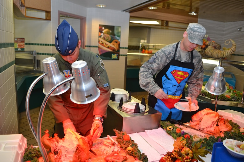 Lt. Col. Ryan Jones, 552nd Training Squadron commander, left, and Master Sgt. Steven Colombo, 552nd TRS first sergeant, serve up turkey to patrons at the Vanwey Dining Facility on Thanksgiving. (Air Force photo by Ron Mullan/Released)