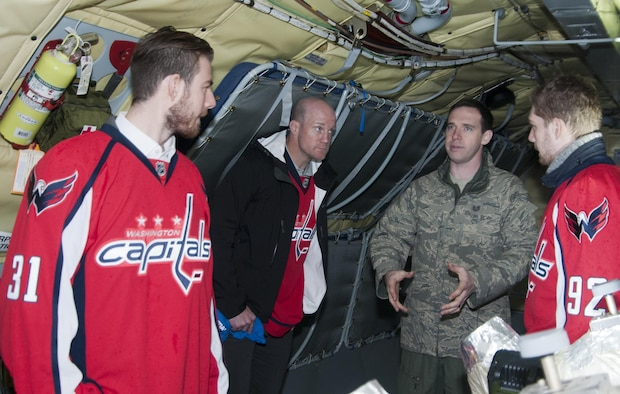 Technical Sgt. Matt Oberlin, 756th Air Refueling Squadron boom operator (right), explains the role and operations of a boom operator to a group of Washington Capitals players on board a 459th Air Refueling Wing KC-135R Stratotanker on Joint Base Andrews, Md., flight line Dec. 1, 2015. . The Capitals visited JBA to learn about the Air Force mission here. They observed special performances by the U.S. Air Force band Max Impact, Honor Guard, 11th Wing Explosive Ordnance Disposal, as well as static displays from the 1st Helicopter Squadron and 459 ARW, 113th Wing, Air National Guard. (U.S. Air Force photo by Staff. Sgt. Kat Justen)