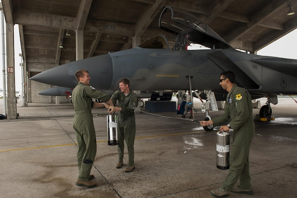 U.S. Air Force Lt. Col. Alexander Haddad, 44th Fighter Squadron pilot, gets sprayed with water by 1st Lts. Maxwell Anthony (left) and Michael Tope, 44th FS pilots, after Haddad reached 2,000 F-15 flying hours at Kadena Air Base, Japan, Nov. 19, 2015. It is a tradition for pilots to get sprayed down with water after reaching a significant milestone. U.S. Air Force photo by Airman 1st Class Corey M. Pettis