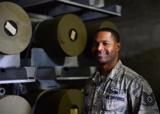 Tech. Sgt. Dan Edwards, 51st Munitions Squadron storage shift lead, poses in front of munition pallets stacked high at Osan Air Base, Republic of Korea, Nov. 17, 2015. MUNS Airmen are responsible for building, storing, maintaining, inspecting and delivering everything from 2,000 pound bombs to 9mm rounds. (U.S. Air Force photo by Staff Sgt. Amber Grimm/Released)