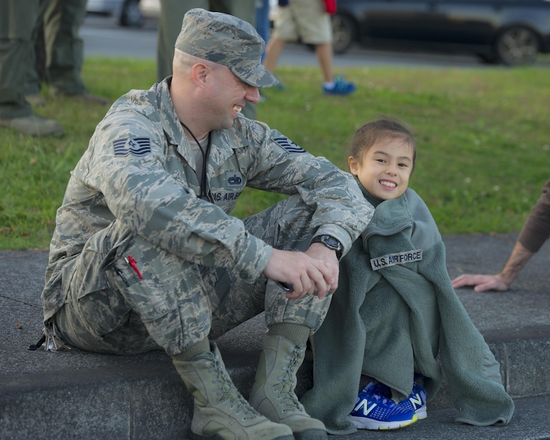 A father and daughter watch the Yokota Holiday Spectacular Parade at Yokota Air Base, Japan, Nov. 24, 2015. The parade consisted of bands from different military branches, the Yokota Car Club, the Scary Blossoms roller derby team, and other attractions. (U.S. Air Force photo/Airman 1st Class Delano Scott)