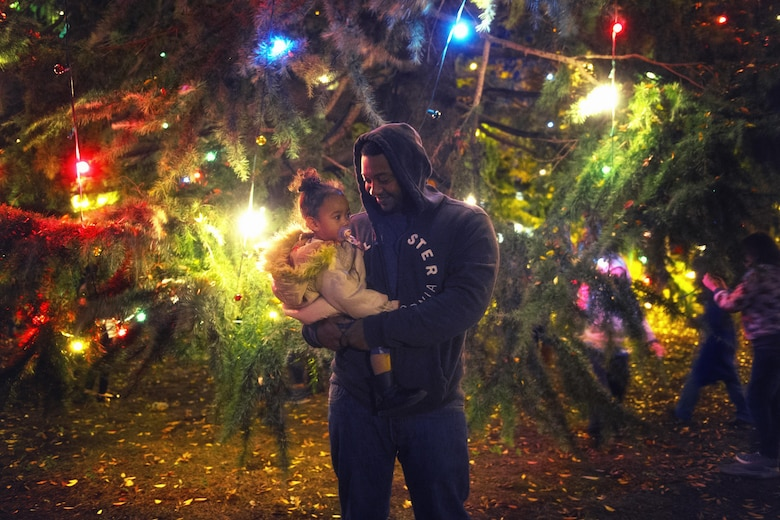 Staff Sgt. Andre Hayes, a 374th Civil Engineer Squadron journeyman, holds his daughter during the holiday tree lighting ceremony at Yokota Air Base, Japan, Nov. 24, 2015. The lighting of the tree signals the beginning of the holiday season. (U.S. Air Force photo/Airman 1st Class Delano Scott)