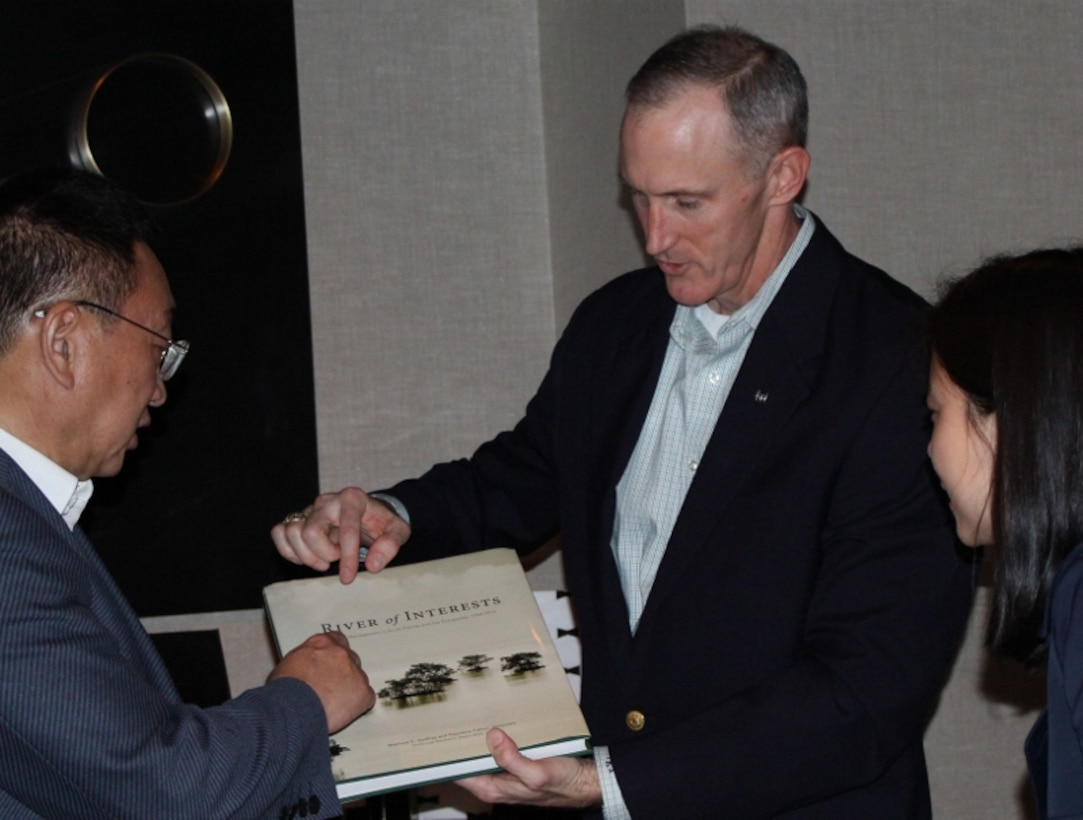 "Jacksonville District Commander Col. Jason Kirk presents Chen Lei, Minister of Water Resources for the People's Republic of China, with ""River of Interests,"" which discusses water management in south Florida and the Everglades between 1948 and 2010."