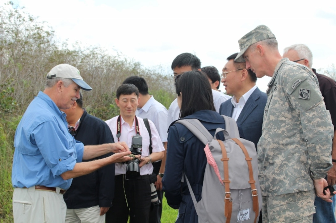 Robert Johnson, Director of the South Florida Natural Resources Center, National Park Service, shows periphyton, the base of the food chain in the Everglades, to Minister Chen Lei, Jacksonville District Commander Col. Jason Kirk, Gao Bo (with camera) and other members of the Chinese delegation during a tour of Shark Valley in Everglades National Park.