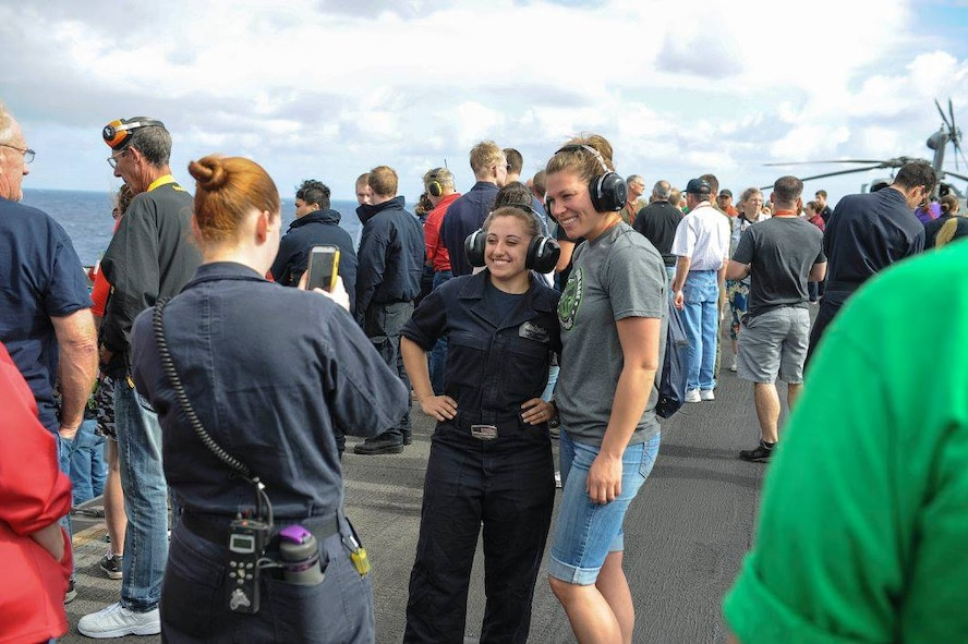 PACIFIC OCEAN – Senior Airman Rose Gudex poses for a photo with her co-sponsor, Electrician's Mate Fireman Nicole LaBruzzo, before a gun power demonstration aboard the USS Theodore Roosevelt, Nov. 19, 2015. Gudex was on the Roosevelt for the 2015 Tiger Cruise where family and friends of Sailors and Marines were able to experience life aboard a ship for the final week of their deployment. Gudex was visiting her twin brother, Electrician's Mate 3rd Class Ray Gudex. (U.S. Navy photo by Mass Communication Specialist 3rd Class Anthony N. Hilkowski)