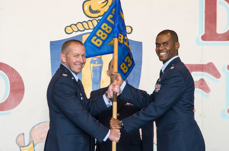 Col. Roger R. Vrooman, 688th Cyberspace Operations Group commander, passes the guidon to Lt Col. Theophilus D. Jackman as he assumes command of the 834th Cyberspace Operations Squadron Dec. 3 at Joint Base San Antonio-Lackland. (U.S. Air Force photo by Johnny Saldivar)