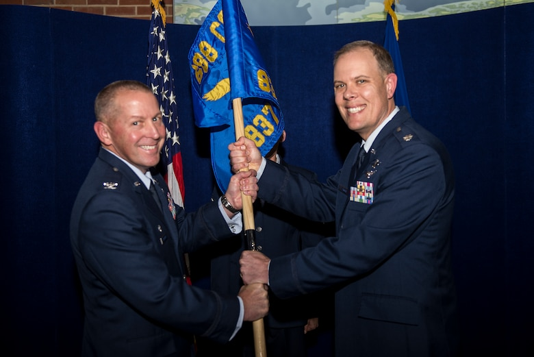 Col. Roger Vrooman, 688th Cyberspace Operations Group commander, passes the guidon to Lt. Col. Kevin Biggs during the 837th Cyberspace Operations Squadron activation ceremony Dec. 1 at Scott Air Force Base, Ill. Biggs will command the 837th responsible for defensive cyberspace operations supporting DOD and Combatant missions. (U.S. Air Force Photo/Senior Airman Jake Eckhardt)