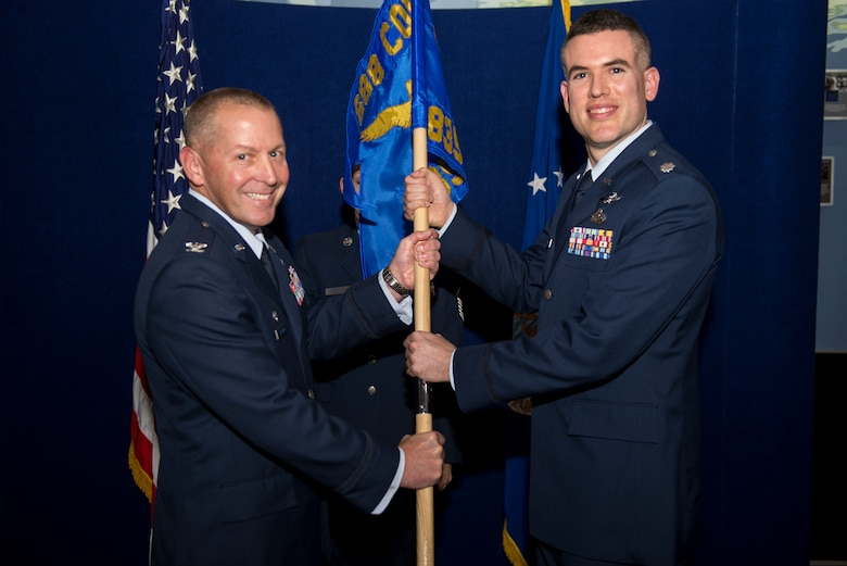 Col. Roger Vrooman, 688th Cyberspace Operations Group commander, passes the guidon to Lt. Col. David Chaboya during the 835th Cyberspace Operations Squadron activation ceremony Dec. 1 at Scott Air Force Base, Ill. Chaboya will lead the 835th  responsible for defensive cyberspace operations supporting Air Force and DOD missions. (U.S. Air Force Photo/Senior Airman Jake Eckhardt)