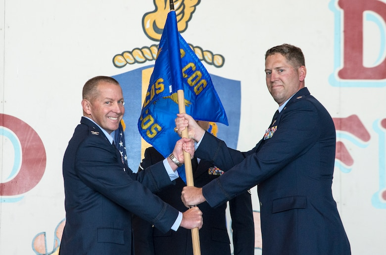 Col. Roger R. Vrooman, 688th Cyberspace Operations Group commander, passes the guidon to Lt Col. Travis G. Howell as he assumes command of the 833rd Cyberspace Operations Squadron Dec. 3 at Joint Base San Antonio-Lackland. (U.S. Air Force photo by Johnny Saldivar)