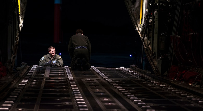 Loadmasters from the 37th Airlift Squadron wait to load cargo onto a C-130J Super Hercules Nov. 25, 2015, at Ramstein Air Base, Germany. The cargo was dropped during an airdrop training mission over U.S. Army Garrison Grafenwoehr, Germany, due to it having one of the largest drop zones in Germany. (U.S. Air Force photo/Staff Sgt. Sara Keller)
