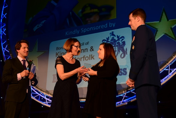 Amanda Gordon, wife of Staff Sgt. Eli Gordon, 492nd Aircraft Maintenance Unit activity security manager, accepts the Armed Services Person of the Year award on her husband's behalf during the Stars of Norfolk and Waveney Awards ceremony at St. Andrews Hall, Norfolk, Dec. 3, 2015. Gordon, who is currently deployed to an undisclosed location, was named the winner for his heroic actions after a Hellenic air force F-16 crashed during Tactical Leadership Program 15-1 in Spain. (U.S. Air Force photo by Senior Airman Erin Trower)
