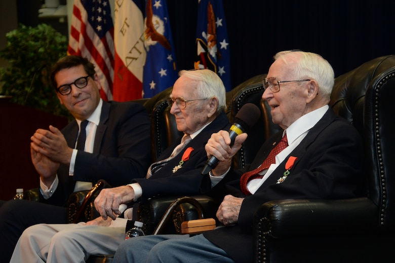 """Retired Air Force Reserve Majs. and 92-year old twin brothers Raymond """"Glenn"""" Clanin (with microphone) and Russell """"Lynn"""" Clanin discuss some of their experiences as pilots of the B-26 Marauder named """"Flak Bait"""" on several missions with the 449th Bombardment Squadron, 322nd Bomb Group, known as """"The Annihilators,"""" while stationed in Beauvais, France. Glenn completed 26 missions while Lynn completed 21 missions in the twin-engine medium bomber. The brothers are recent recipients of the French government's highest distinction for their military service as World War II veterans, the Legion of Honor medal. (U.S. Air Force photo/Van De Ha)"""