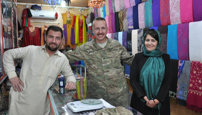 U.S. Army Staff Sgt. Matthew Amon and project managers of a local orphanage in Kabul, Afghanistan, pose for a photo at a store in the base bazaar. Amon, a security forces squad leader at Train, Advise, Assist Command-Air (TAAC-Air), met the couple and helped set-up a school supply drive with family and friends back home in Texas to donate to children at a local orphanage.  Amon is deployed from the 442nd Engineer Company as part of the Texas Army National Guard.  (U.S. Air Force photo by Capt. Eydie Sakura/released)