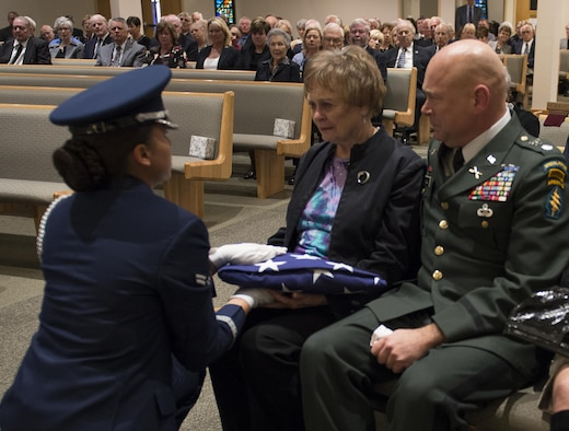 A member of the Eglin Air Force Base Honor Guard presents a folded American flag to Judy Haugen, the widow of retired Brig. Gen. Donald Haugen, during a memorial ceremony Dec. 5 at Crosspoint Methodist Church in Niceville, Fla.  The 84-year-old Haugen, who passed away Dec. 1, was the first commander of a 919th designated unit assigned to Duke Field, the 919th Tactical Airlift Group.  The designation still resides there today with the special operations Reserve unit, 919th Special Operations Wing, still resides there today.  Many of the tactical airlift capabilities that began under his leadership are still part of the current 919th SOW mission.  (U.S. Air Force photo/Tech. Sgt. Jasmin Taylor)