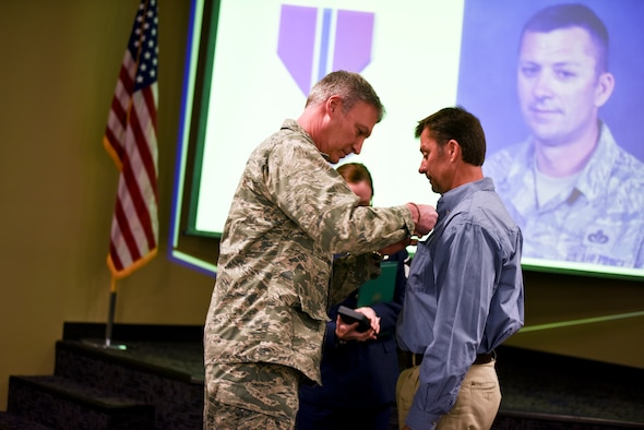 Brig. Gen. Kurt Vogel, commander of the Arkansas Air National Guard, pins a Bronze Star medal onto the shirt of former 188th member Master Sgt. Paul Fair. Fair was awarded the Bronze Star medal for his role as an Agribusiness Development Team member with the 87th Troop Command during Operation Enduring Freedom from Jan. 2010 to Jan. 2011. (U.S. Air National Guard photo by Capt. Holli Nelson/released)