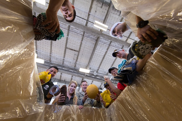 (Center) Brig. Gen. Andrew Toth, 36th Wing Group commander, and volunteers throughout the local community place relief items into a box while sorting donations for Operation Christmas Drop at Andersen Air Force Base, Guam, Dec. 5, 2015. More than 40,000 pounds of goods will be dropped to 56 islands throughout the Commonwealth of the Northern Marianas, Federated States of Micronesia and Republic of Palau during Operation Christmas Drop 2015, the longest running Department of Defense humanitarian airdrop mission. (U.S. Air Force photo by Osakabe Yasuo/Released)