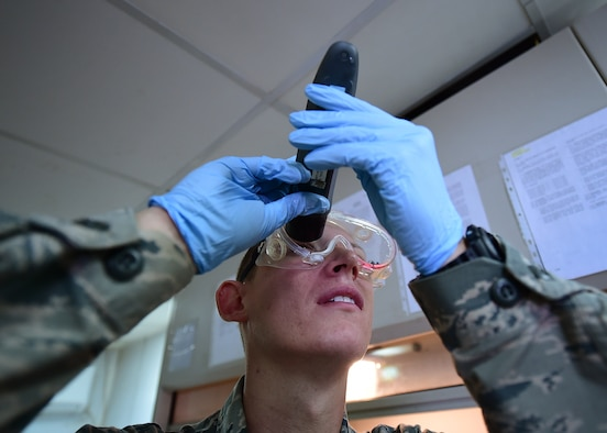 Senior Airman Nickolauss Guier, a 386th Expeditionary Logistics Readiness Squadron fuels systems journeyman, looks through a refractometer while conducting a Fuel System Icing Inhibitor test at an undisclosed location in Southwest Asia, Dec. 1, 2015. The POL flight is responsible for providing fuel to all aircraft, and ground equipment for U.S. and coalition forces on base in support of Operation INHERENT RESOLVE. (U.S. Air Force photo by Staff Sgt. Jerilyn Quintanilla)