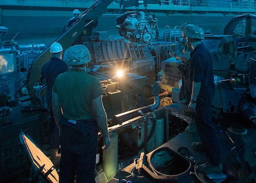 U.S. Marines with Light Armored Reconnaissance Company, Battalion Landing Team 2/6, 26th Marine Expeditionary Unit, use a crane mounted on a light armored vehicle to maneuver an LAV engine aboard the amphibious assault ship USS Kearsarge Dec. 4, 2015. Repairmen with the company serviced an LAV engine with an oil leak. The 26th MEU is embarked on the Kearsarge Amphibious Ready Group and is deployed to maintain regional security in the U.S. 5th Fleet area of operations.