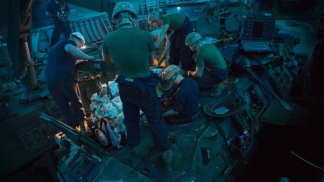 U.S. Marines with Light Armored Reconnaissance Company, Battalion Landing Team 2/6, 26th Marine Expeditionary Unit, attach a light armored vehicle engine to an LAV aboard the amphibious assault ship USS Kearsarge Dec. 4, 2015. Repairmen with the company serviced an engine with an oil leak. The 26th MEU is embarked on the Kearsarge Amphibious Ready Group and is deployed to maintain regional security in the U.S. 5th Fleet area of operations.