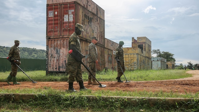 U.S. Marine Sgt. Sean O'Hair (middle), a combat engineer with Special-Purpose Marine Air-Ground Task Force Crisis Response-Africa, leads Uganda People's Defense Force soldiers through a notional improvised explosive device lane during IED awareness training at Camp Singo, Uganda, Nov. 3, 2015. All UPDF soldiers went through IED awareness training before they split into their military occupational specialties-specific training. This type of training is important for all the soldiers as one of the greatest threats in the African Union Mission in Somalia are IEDs.