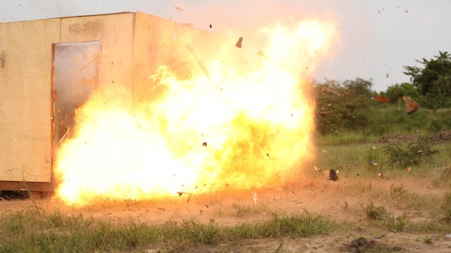 A Uganda's People Defense Force soldier detonates an oval charge on the wall of a notional objective position of desired entry while the team seeks cover around the corner of the position at Camp Singo, Uganda Nov. 25, 2015. This type of charge is used to create a hole through a wall when there is no available entrance or to gain the element of surprise. The Marines and UPDF improved breaching capabilities as they prepare for their African Union Mission in Somalia.