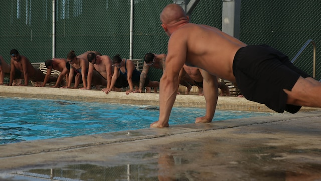 Gunnery Sgt. Brandon Soetaert, the chief instructor trainer for Marine Corps Instructor Course of Water Survival with Expeditionary Warfare Training Group, Pacific, executes push-ups with students of MCICWS at the base pool aboard Marine Corps Base Hawaii, Dec 1, 2015. MCICWS is a course for noncommissioned officers and higher to become water survival instructors, whose purpose is to make sure Marines are safe during basic swim qualification.