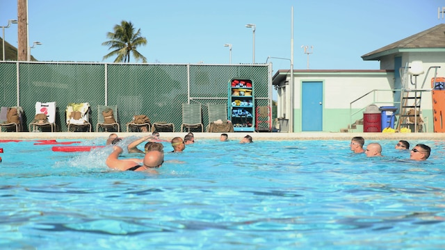 Students in Marine Corps Instructor Course of Water Survival practice rescuing a victim from drowning at the base pool aboard Marine Corps Base Hawaii, Dec. 1, 2015. MCICWS is a course for noncommissioned officers and higher to become water survival instructors, whose purpose is to make sure Marines are safe during swim qualification.