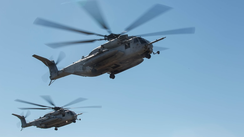 Two CH-53E Super Stallions fly over a landing zone  during section Confined Area Landings board Marine Corps Base Camp Pendleton, Calif., Dec. 2, 2015. Marines with HMH-361 conducted section Confined Area Landings and Field Carrier Landing Practices to fulfill training requirements for landing aboard a Navy ship.