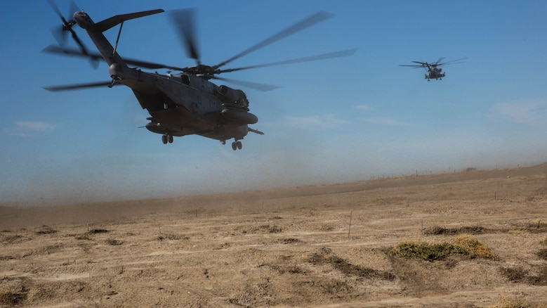 Two CH-53E Super Stallions take off during section Confined Area Landings board Marine Corps Base Camp Pendleton, Calif., Dec. 2, 2015. Marines with HMH-361 conducted section Confined Area Landings and Field Carrier Landing Practices to fulfill training requirements for landing aboard a Navy ship.