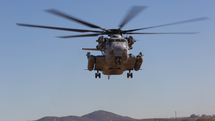 A CH-53E Super Stallion with Marine Heavy Helicopter Squadron 361 hovers over a landing pad during Field Carrier Landing Practices aboard Marine Corps Air Station Miramar, Calif., Dec. 2, 2015. Marines with HMH-361 conducted section Confined Area Landings and Field Carrier Landing Practices to fulfill training requirements for landing aboard a Navy ship.