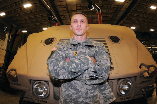 Army Sgt. 1st Class Chad Corey, an instructor assigned to the Basic Wheel Division, Wheel Maintenance Training Department, Ordnance School, at Fort Lee, Va., stands near a Humvee in the bay area of Stever Hall on the Ordnance Campus. Corey submitted an idea through the Supply and Maintenance Assessment and Review Team Program that could save the Army thousands of dollars in parts replacement costs for the vehicle and others. He was recognized for his suggestion by the Ordnance School leadership Nov.16 during an awards presentation. U.S. Army photo by Terrance Bell