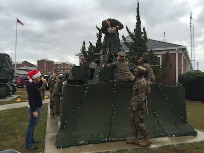 Marines and Family Readiness volunteers string up lights on one of the bulldozers in front of the Marine Corps Engineer School headquarters building in order to decorate for the holidays at Courthouse Bay, Camp Lejeune, N.C.