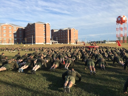 Marines from Marine Corps Engineer School (MCES) perform Marine Corps push-ups as part of a group of warm-up exercises prior to the MCES Holiday Fun Run on Dec. 4, 2015 at Courthouse Bay, Camp Lejeune, N.C.